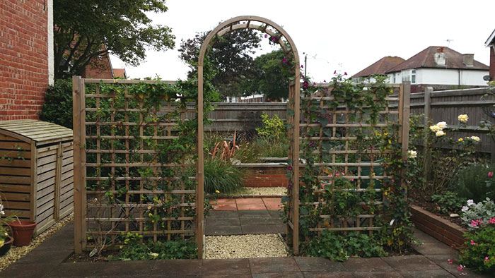 A trellis and arch divides the space